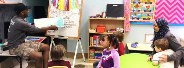 Pre-school students listen to male teacher reading story