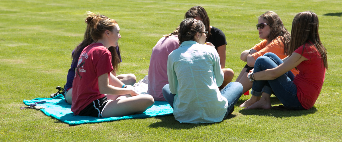 students relaxing on green space.