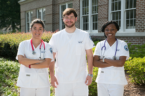 three student nurses posing in front of building