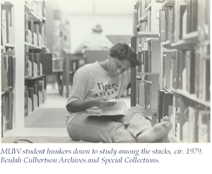 black and white image of a student studying barefoot in the stacks