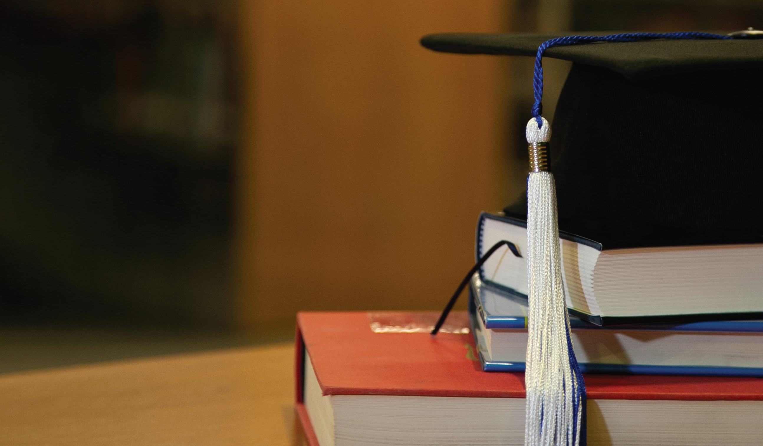 mortar board on top of books
