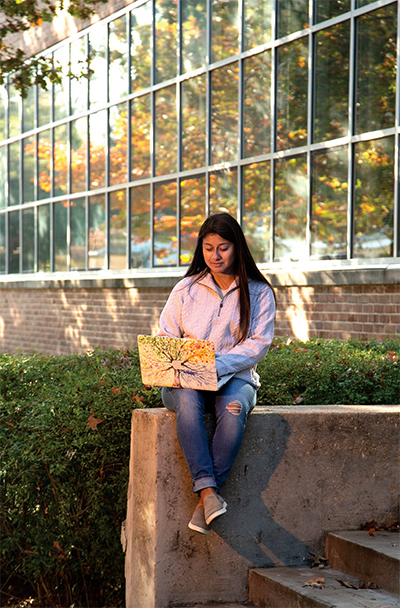 female student on laptop outdoors