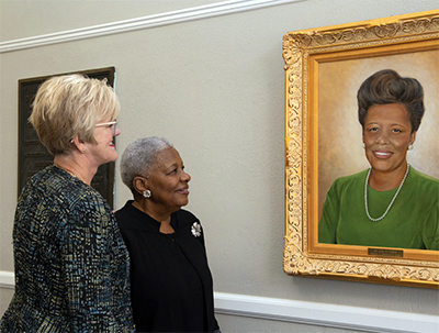 President Nora Miller with Dr. Alma Turner, looking at painting of Dr. Turner