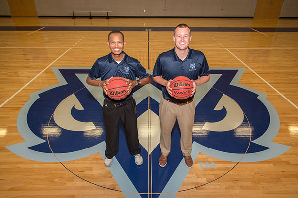Coach White and Coach Merkel hold basketballs on the Owls home court