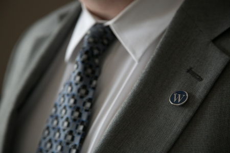 W lapel pin on suit